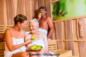 Eine ältere Frau und ein junges Paar schwitzen in der Sauna.
